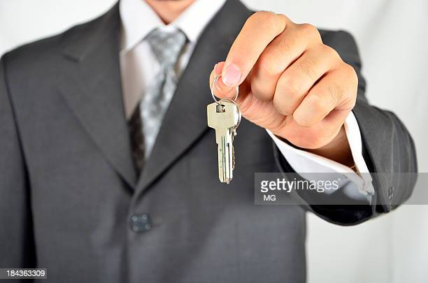 A business man holding out a key