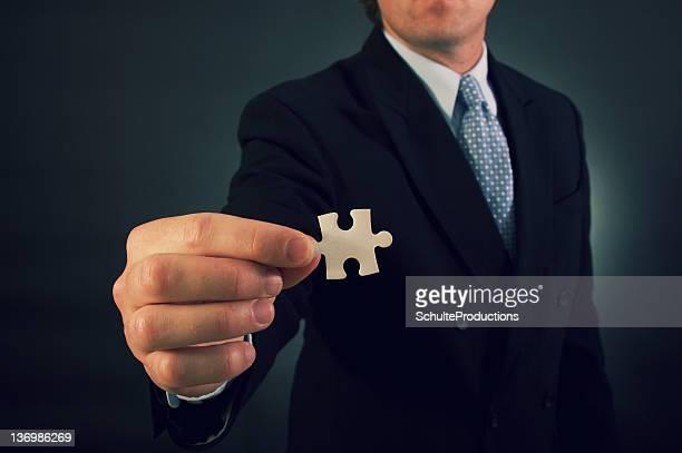 Homme d'affaires tenant la pièce du Puzzle
