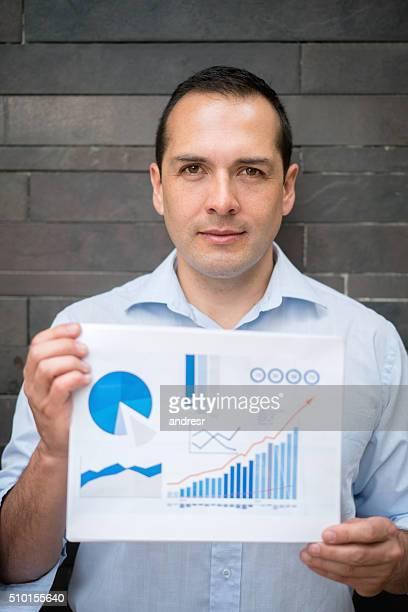 Business man holding statistics graphs