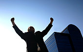 Business man holding up his arms in victory with a blue office building in the background