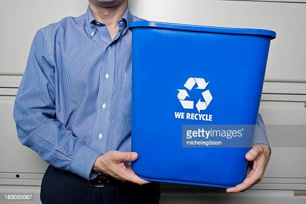 Business man holding up recycling bin