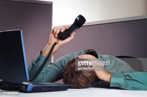 Business man holds head and phone in the air
