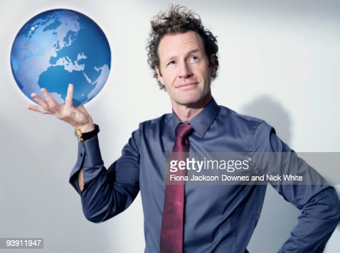Business man holds up globe : Stock Photo