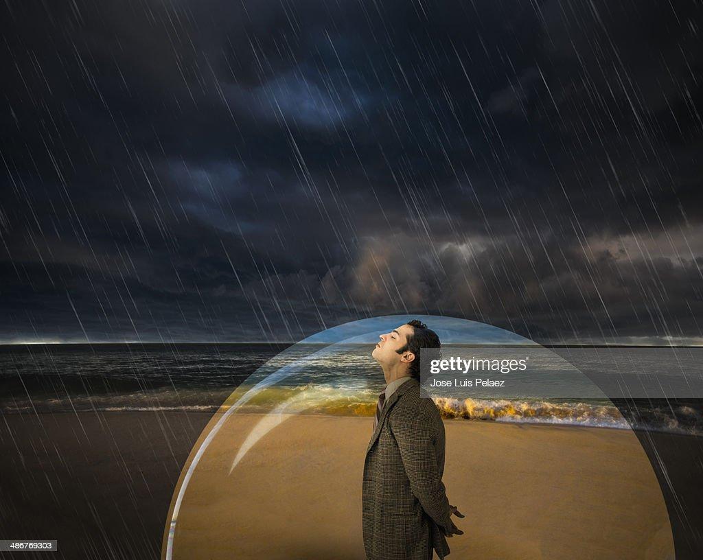 Business man in a bubble while raining : Foto de stock