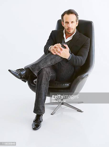 Business man in black chair (hands on knee)