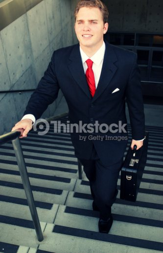 d1e09c35d065 Business man in black suit and red tie smiles as he walks up the stairs :