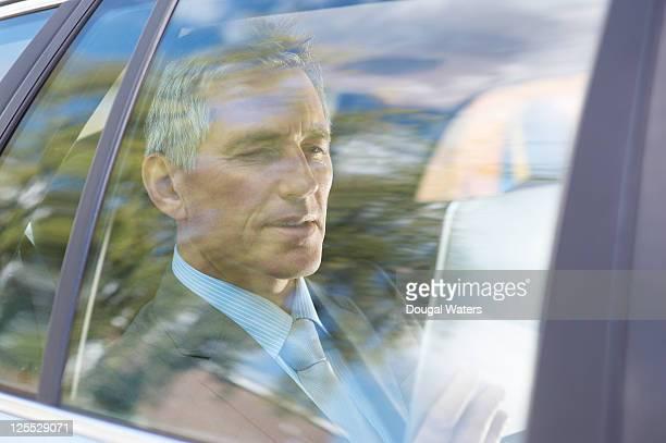 Business man in car using digital tablet.