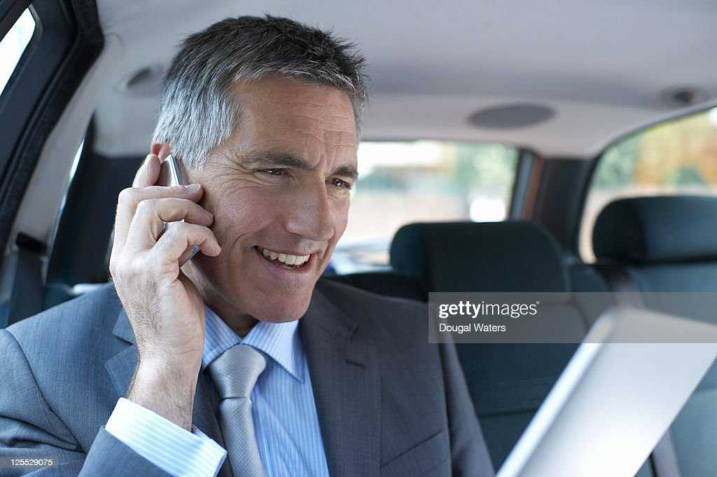 Business man in car using phone and digital tablet : Stock Photo
