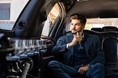 Business man in limousine with glass of champagne, enjoying