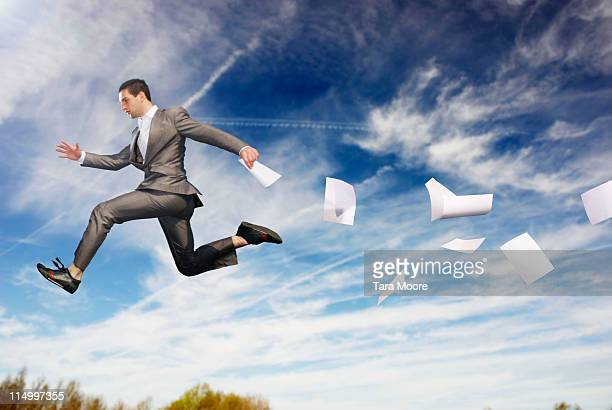 business man in mid air with paper