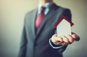 Business man in suit having miniature house on palm of his hand - Business mortgage, property loan, house insurance, business investment concept.