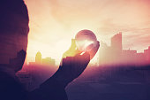 Business man in suit with cityscape montage. The man is unrecognizable and you cannot see his face. He is superimposed onto a city skyline at sunset. He is holding a world map globe like a crystal bal