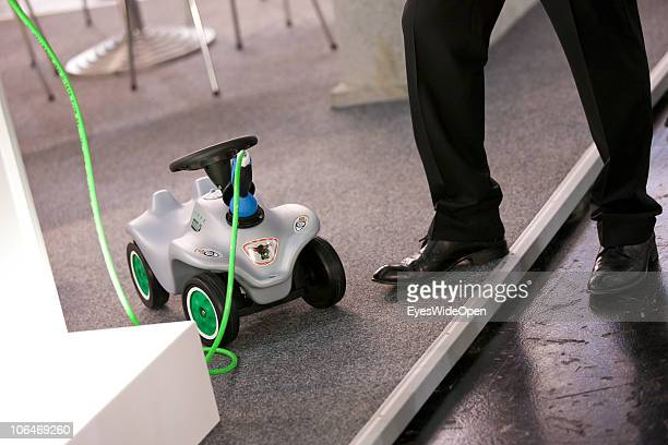 A business man is waiting while charging his bobby car during the eCarTec 2010 the 2nd International trade fair for electric mobility at the New...
