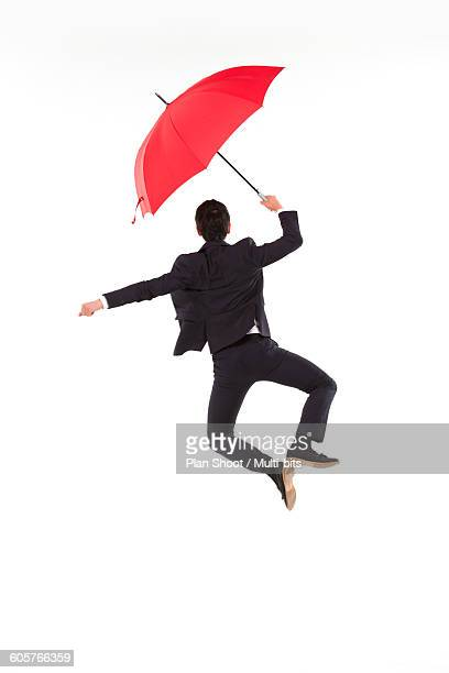 business man jumping with red umbrella