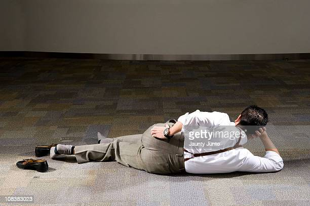 business man laying down on the floor