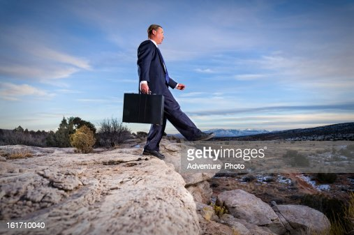 Business Man Leaping Off Fiscal Cliff