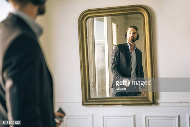 Business man listening music in front of mirror