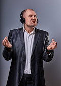 Business man listening the music in wireless earphone and trying relax he showing the hands yoga sign zen on grey studio background. Closeup portrait