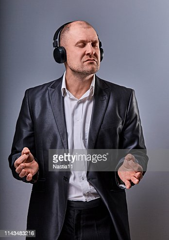 Business man listening the music in wireless earphone and trying relax he showing the hands yoga sign zen on grey studio background. Closeup : Stock Photo