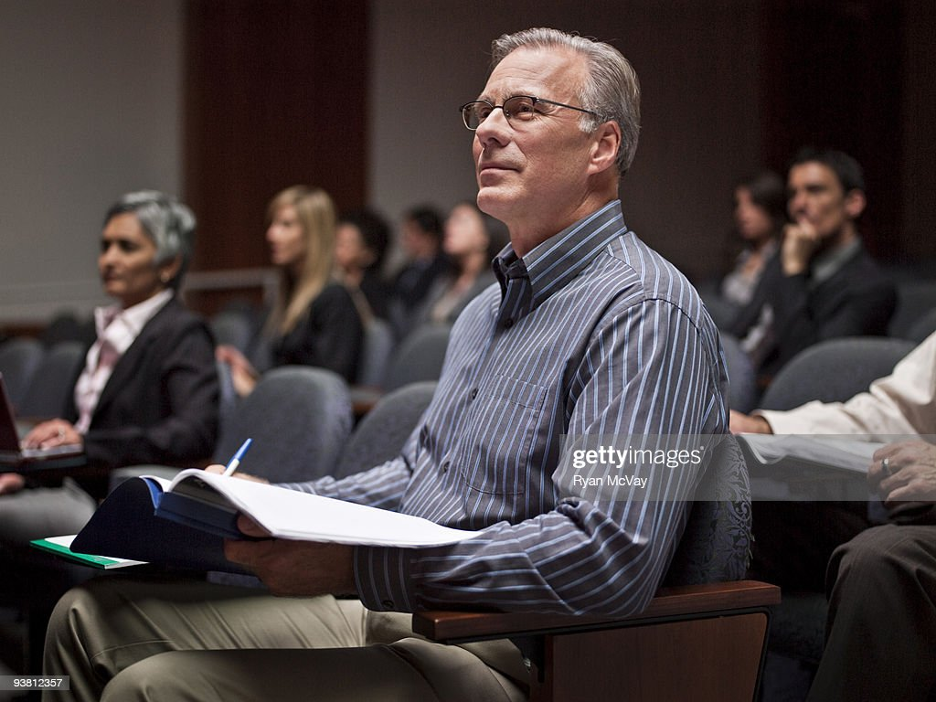 Business man listening to speaker in auditorium