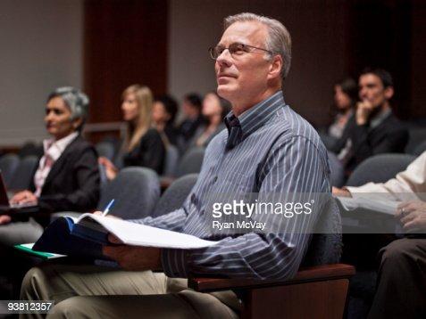Business man listening to speaker in auditorium