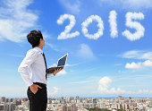 Young business man using laptop and look to 2015 year text with blue sky and cloud and cityscape .