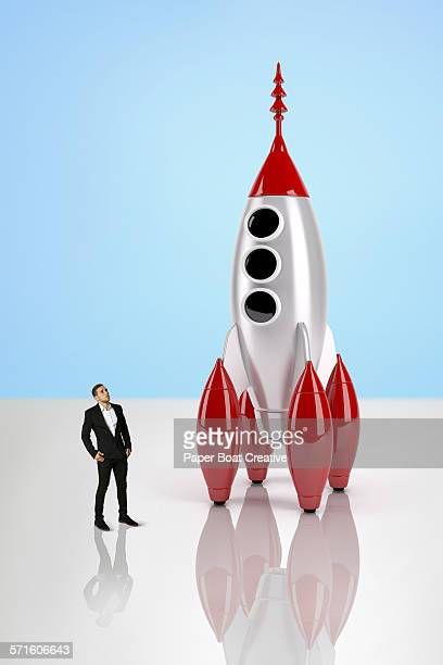 Business man looking at a giant toy rocket ship