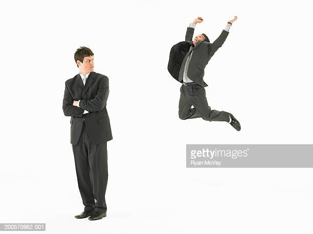 Business man looking at colleague jumping