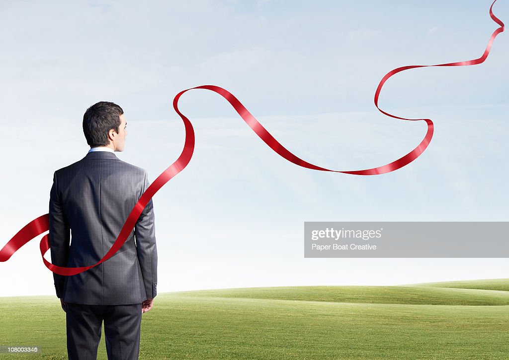 Business man looking at floating red ribbon