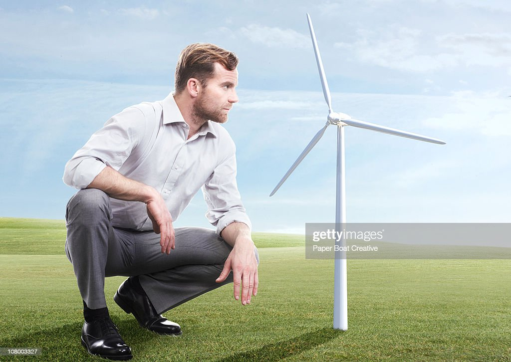 Business man looking at modern windmill : Stock Photo