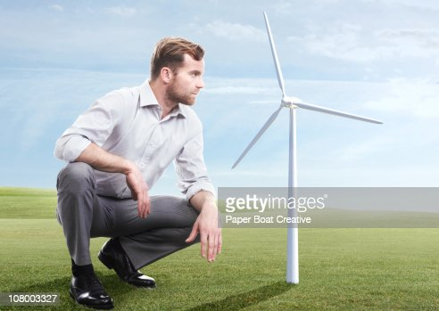 Business man looking at modern windmill