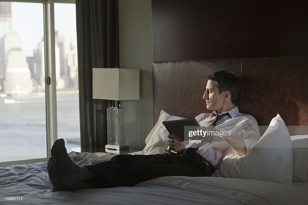 Business man looking off holding digital tablet