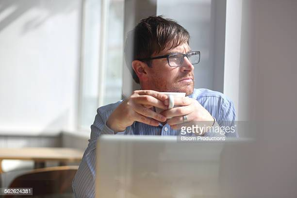 Business man looking out of window in a cafe