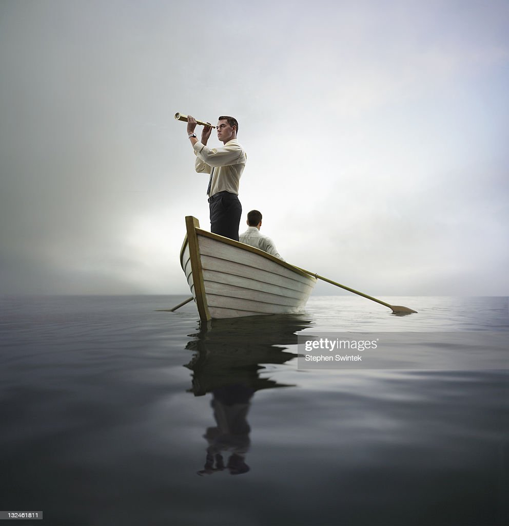 business man looking through spyglass in a boat : Stock Photo