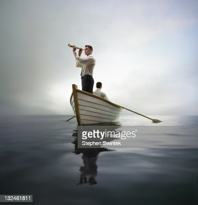 business man looking through spyglass in a boat