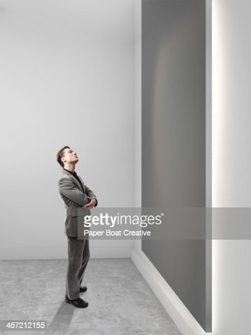 Business man looking up at blank grey canvas
