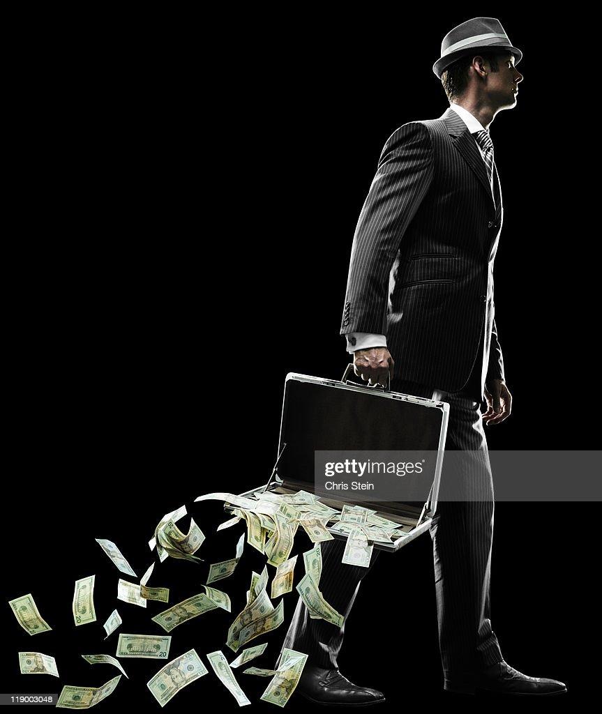 Business man losing money as he walks