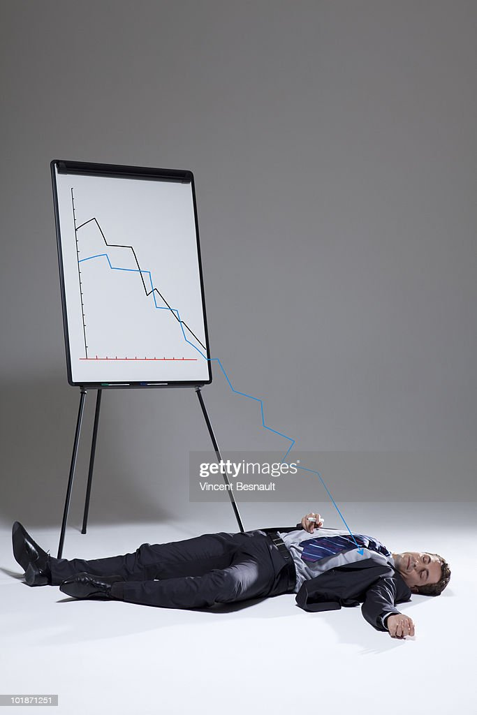 Business man lying in front of his paper board : Stock Photo