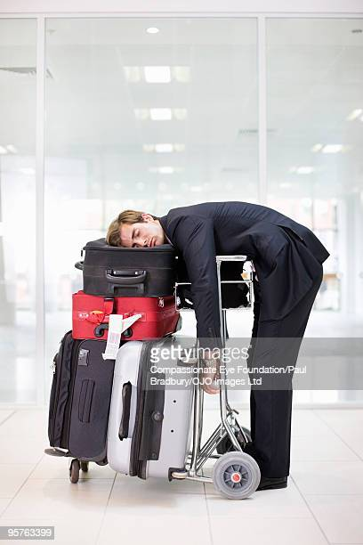 Business man lying on luggage at an airport