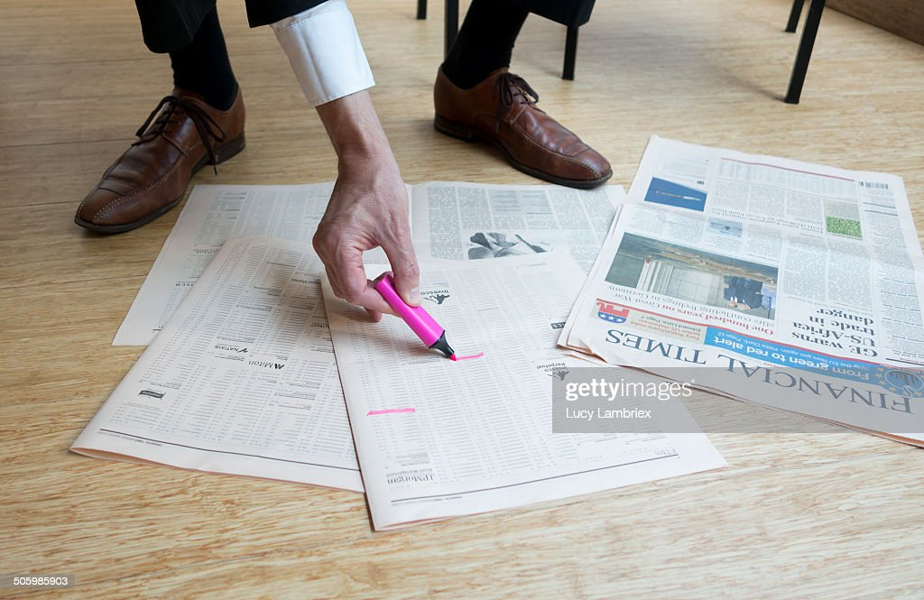 Business man marking stock in Financial Times spread out on floor.