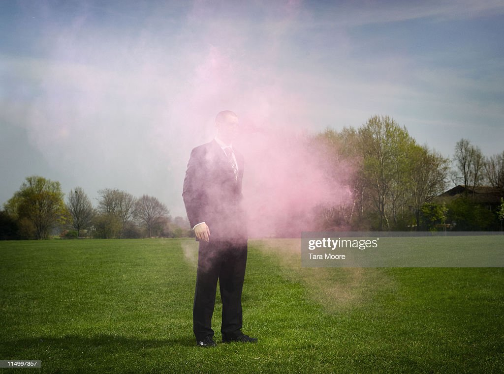 business man obscured by pink smoke : Stock Photo