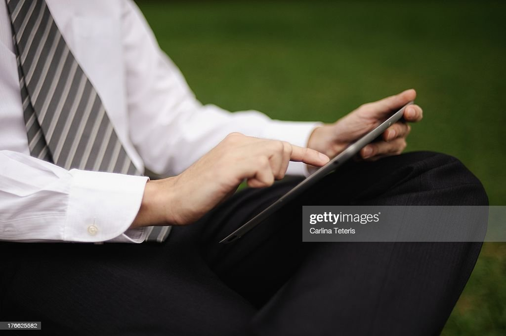 Business man on a park bench with a tablet : Stock Photo