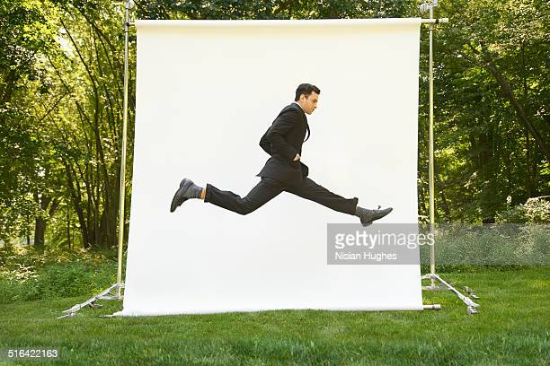 Business man on backdrop in nature jumping