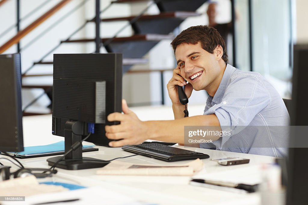 Business man on call while looking at computer : Stock Photo
