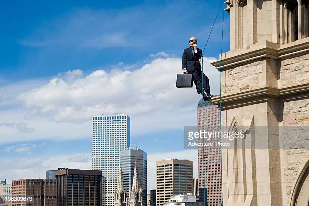 Business Man on Rope in Suit Hanging Off Building