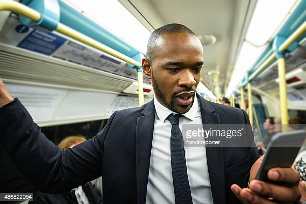 Homme d'affaires sur le téléphone à l'intérieur de la station de métro de métro de Londres