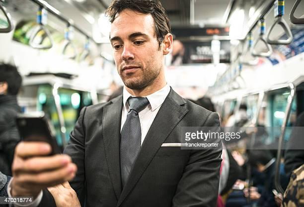 ビジネス男は電話を東京の地下鉄