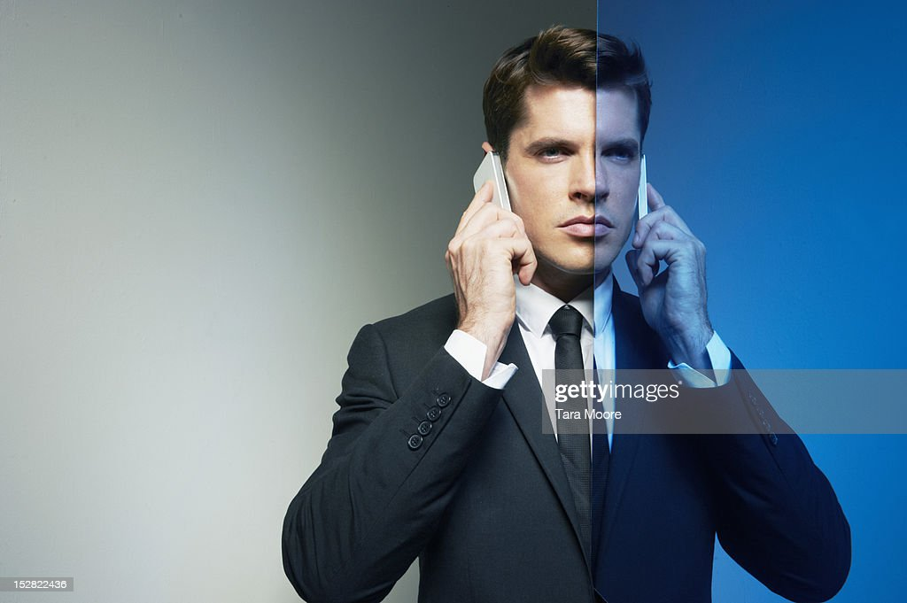 business man on two phones with mirror image : Stock Photo