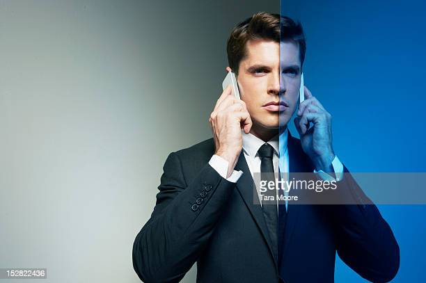 business man on two phones with mirror image