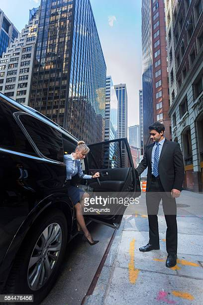 Business man opening car door for woman